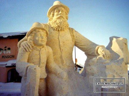 Die Skulptur zeigt einen sitzenden Wanderer mit seinem Sohn im Arm. Er hält sich an einem Felsen an.