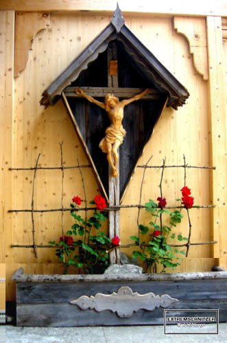 Jesus am Kreuz in einem Marterl aus Holz.