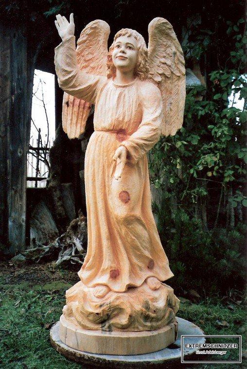 Ein Engel aus Holz der mit der rechten Hand in den Himmel zeigt