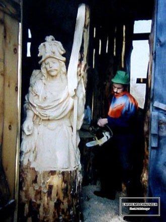 Ernst Adelsberger bei der Arbeit mit der Motorsäge. Er ist gerade dabei, den heiligen Florian aus einem Baumstamm auszuschnitzen.