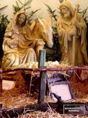 Diese lebensgroße Krippe aus Holz zeigt Maria, Josef, das Jesuskind sowie einen Esel. Am Boden liegt Stroh, im Hintergrund stehen Tannenzweige.