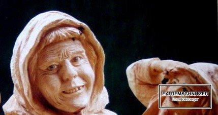 Eine lächelnde alte Frau mit Kopftuch als Porträtfigur aus Holz.
