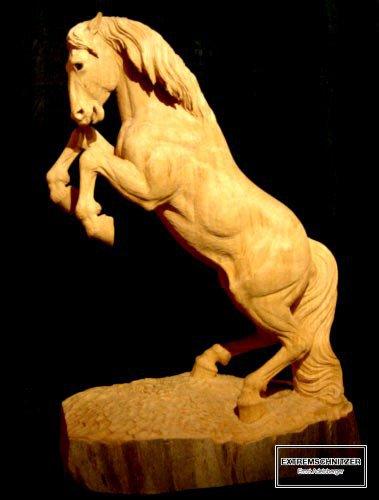 Holzfigur eines Pferdes, das auf den Hinterbeinen steht.
