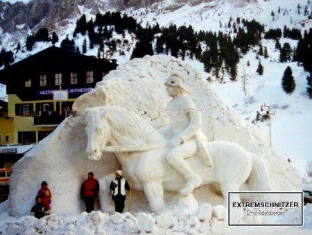 Ein römischer Legionär auf seinen Pferd. Eine Skulptur komplett aus Eis und Schnee. Zum Größenvergleich stehen einige Menschen davor.
