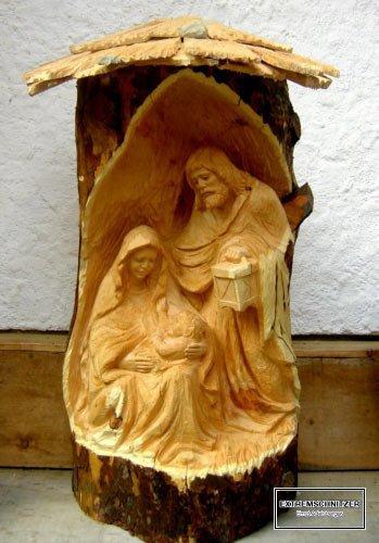 Maria, Josef und Jesus in einer Krippe, die aus einem Holzstamm herausgesägt wurde.