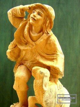Holzfigur eines Hirten, der gerade ein Schaft streichelt und nach irgendetwas Ausschau hält.