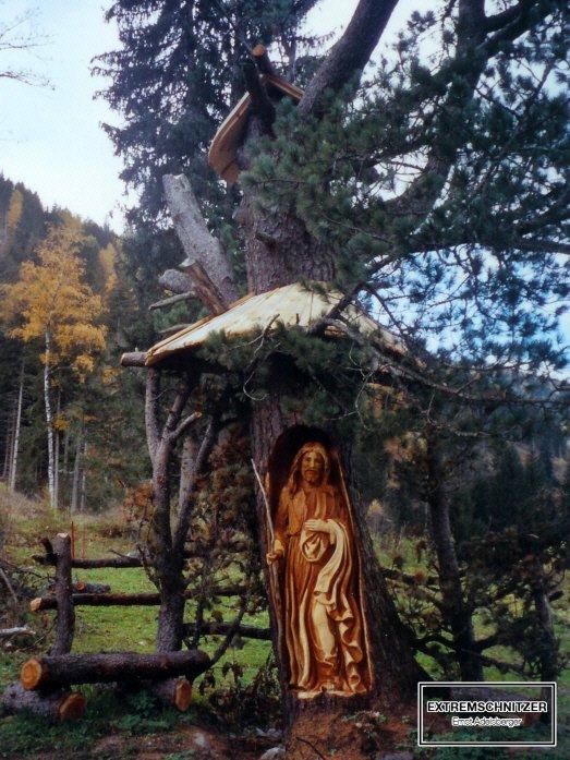 Jesus als guter Hirte aus einem Baumstamm herausgeschnitzt.